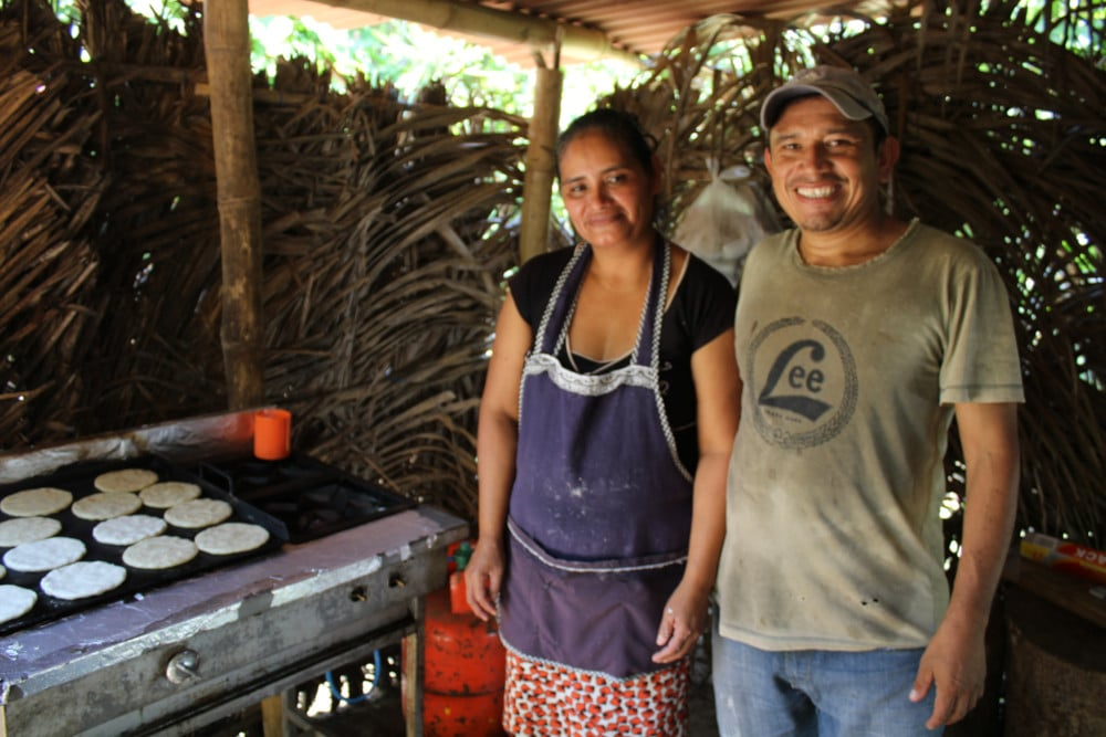 Sandra and Jose in the stand they built to sell tortillas and pupusas